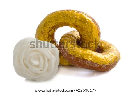 Two golden donuts like rings with a white rose - stock photo