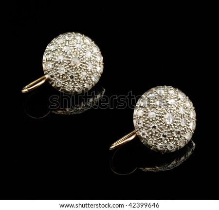 Two golden earrings with diamonds over black background - stock photo