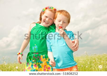 Two golden-haired children playin the field - stock photo