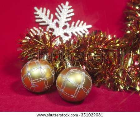 Two golden New Year's balls and ribbon on a red background - stock photo