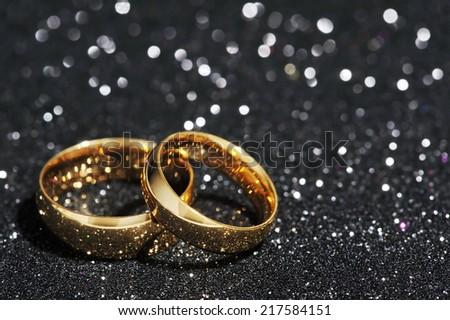 Two golden rings on black glitter background - stock photo