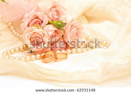 two golden rings on the background of delicate roses and pearls - stock photo