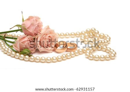 two golden rings, pearls and flowers on white background - stock photo