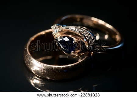 Two golden rings with sapphire and diamonds isolated on black with reflection, light painting, full frame camera shot - stock photo