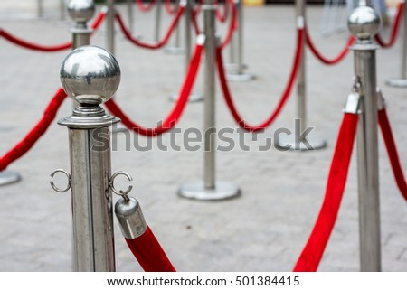 Two golden stanchions with a red rope. Isolated on white background. Barrier, enclosed VIP area, protected enterance, private event, luxury gala concept.