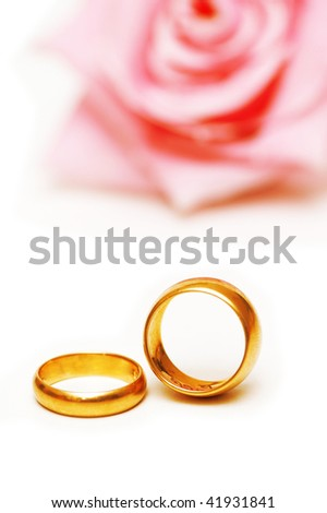 Two golden wedding  rings and a pink rose - stock photo