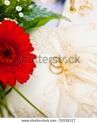 Two golden wedding rings lying on the pillow - stock photo