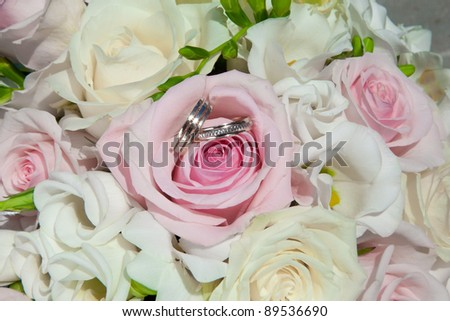 Two golden wedding rings on bouquet of bride