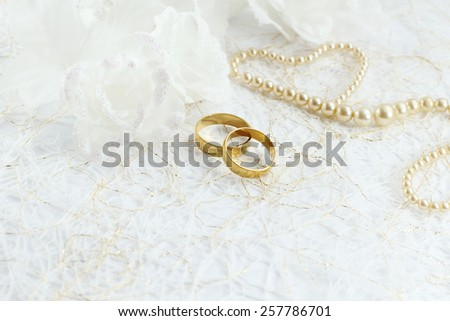 Two golden wedding rings with seamless flower decorations - stock photo