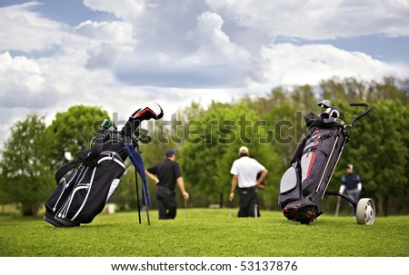 Two golf bags standing in front of a group of golf players putting on green. - stock photo