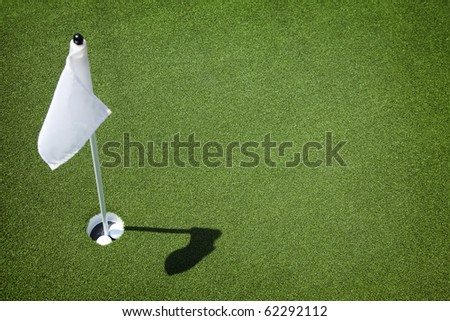 Two golf balls sit inside cup on golf course putting green with flag. - stock photo