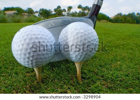 two golf balls teed for one drive for efficiency