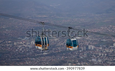 Two gondolas with a city in the background