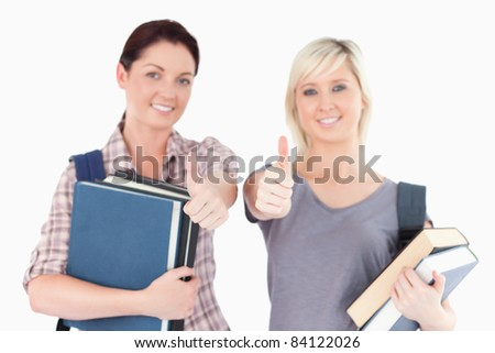 Two gorgeous female students with books and thumbs up