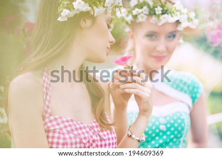 Two gorgeous flower nymphs in blooming garden - stock photo