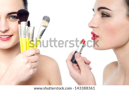 Two gorgeous teen girls applying make-up. - stock photo