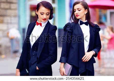 two gorgeous women posing in black suits - stock photo