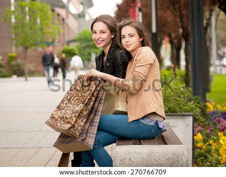 Two gorgeous young brunettes holding shopping bags. - stock photo