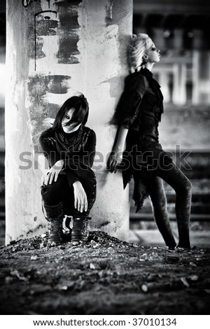 Two goth women at the column. Contrast black and white colors. - stock photo