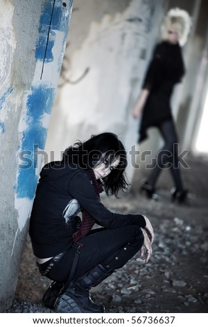 Two goth women at the columns. Focus on front woman. - stock photo