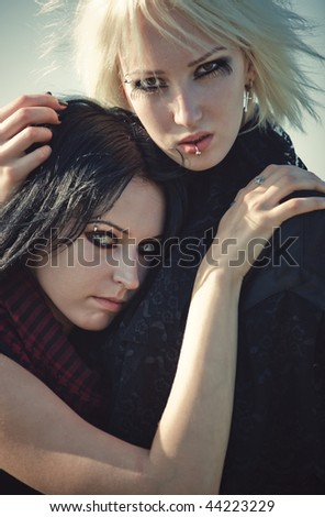 Two goth women concept portrait. Soft yellow and blue tint. - stock photo
