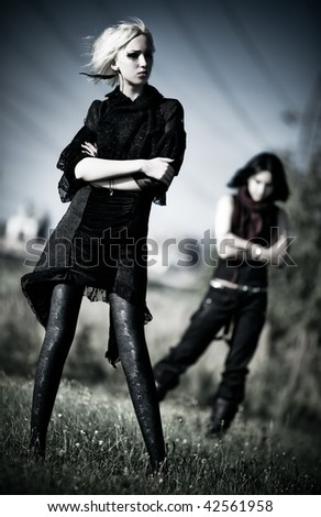 Two goth women outdoors. Contrast colors. - stock photo