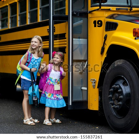 Two grade school girls getting on school bus for first day of school. - stock photo