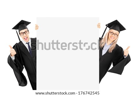 Two graduate students standing behind blank panel and giving thumbs up isolated on white background - stock photo