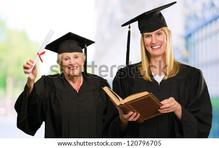 Two Graduate Woman, Outdoors - stock photo