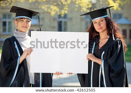 Two graduates hold a clean sheet - stock photo