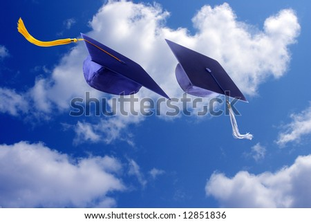 Two graduation caps against blue sky - stock photo