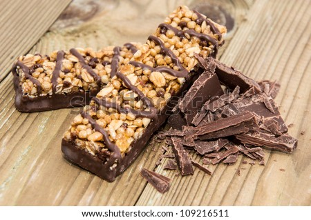 Two Granola Bars with Chocolate on wooden background - stock photo