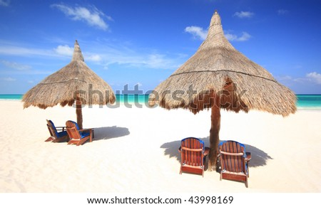 Two grass umbrellas with chairs on a stunning tourist resort beach. Travel & tourism collection.