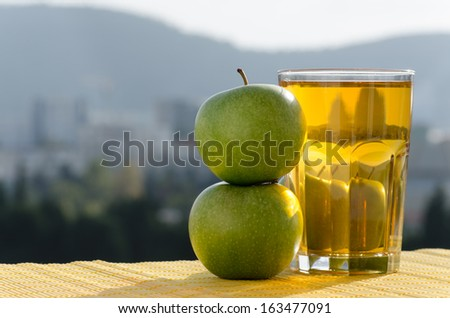 Two green apples and a glass of apple juice are in the right part of the shot in natural light