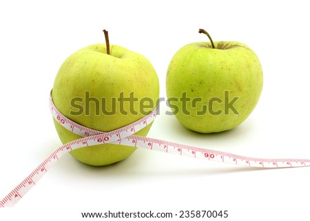 Two green apples, one of which is wrapped with a tape measure - stock photo