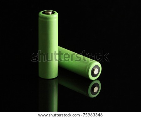 Two green batteries on a glass table. - stock photo
