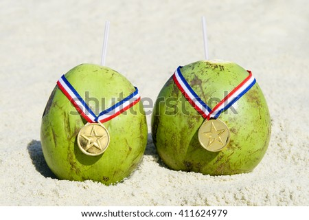 Two green Brazilian coco gelado drinking coconuts wear gold medals on Ipanema Beach in Rio de Janeiro, Brazil
