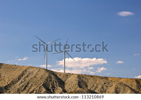 Two green energy wind turbines operating on a hillside