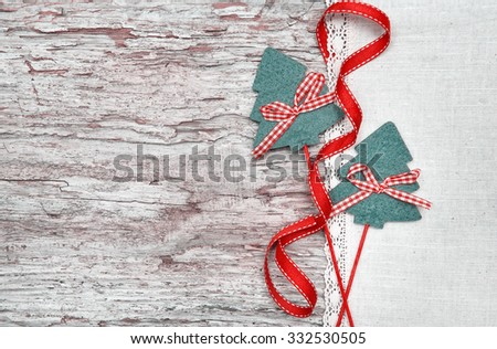 Two green fir tree with ribbon on the linen cloth and old wood background - stock photo