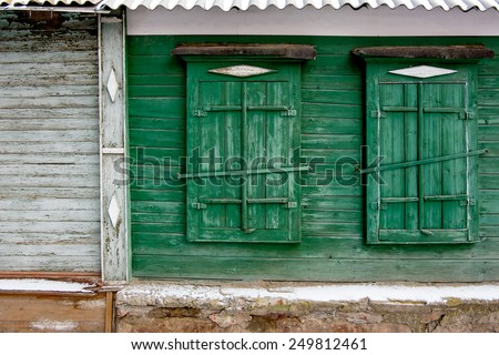 Two green old wooden window in a painted wall in Astrakhan, Russia. - stock photo
