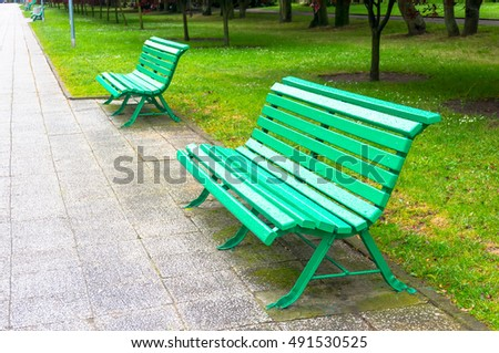 Two green wooden park benches next to sidewalk