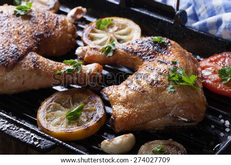 Two grilled chicken legs and vegetables on the grill pan macro. horizontal
