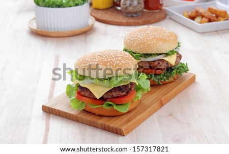 Two grilled homemade hamburgers on a wooden board in environment from the breakfast table. - stock photo