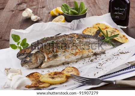 Two grilled trouts on white plate with lemon pieces, potatoes and balsamico on kitchen towel on wooden table. - stock photo