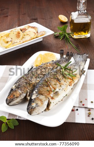 Two grilled trouts on white plate with lemon pieces, potatoes and olive oil on kitchen towel on wooden table. - stock photo