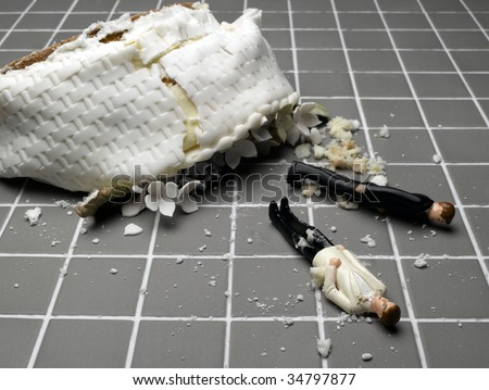 Two groom figurines lying at destroyed wedding cake on tiled floor