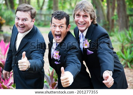 Two grooms and their minister giving a thumbs up at their gay wedding.