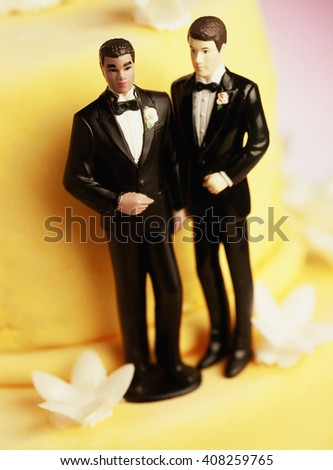 Two grooms, figurines on a yellow wedding cake/Gay Marriage - stock photo