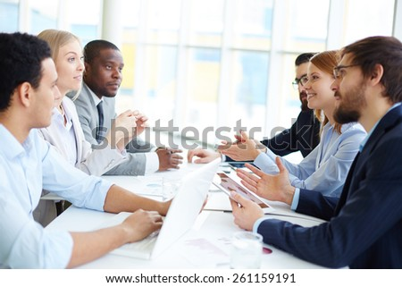 Two groups of people sitting opposite and communicating - stock photo