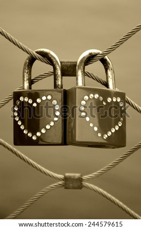Two grungy love padlocks with heart decoration attached to the bridge in Paris. Valentine's day background. Aged photo. Sepia. - stock photo